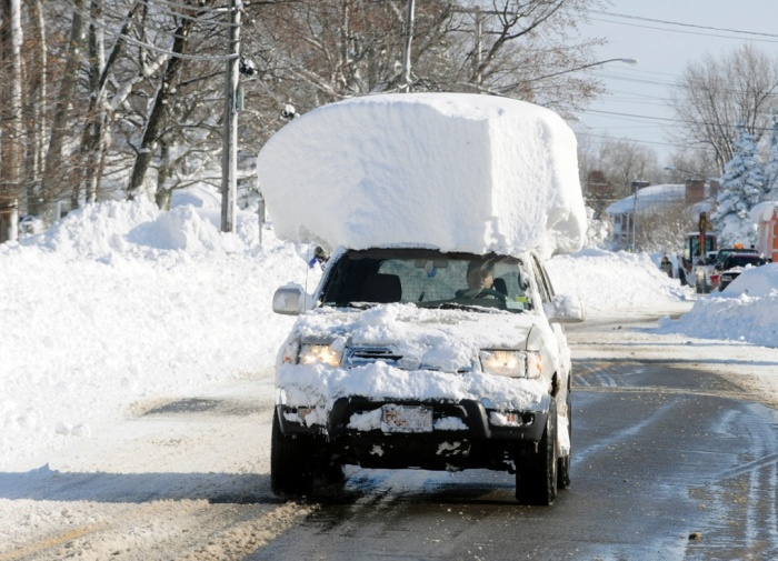 A snow-covered car drives on Broadway, a few miles from our house. Foto: Gary Wiepert/AP