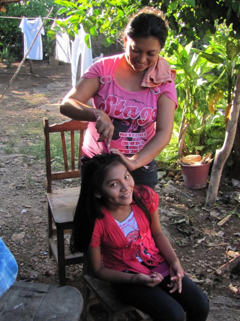Mundy's sister, Aurelia, grooms her daughter's hair.